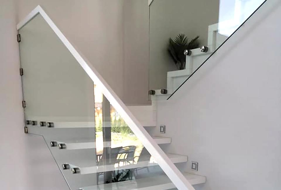 Białe schody ze szklaną balustradą